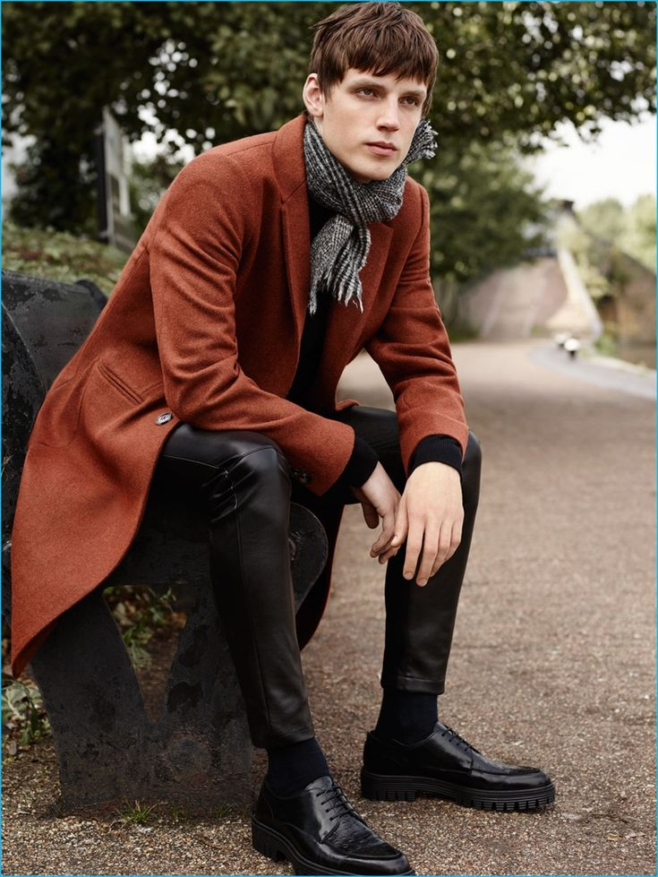 Callum Ward sports a single-breasted coat with a cashmere sweater, faux leather pants, and bluchers from Zara Man.