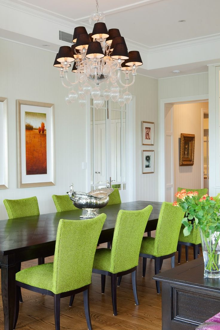 Dining room featuring a 10 seater dining table, upholstered dining chairs and a large chandelier with black shades.