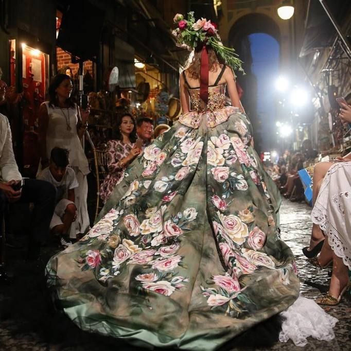 A Napoli la sfilata di Dolce e Gabbana Alta Sartoria dedicata a Sophia Loren prende il via dalla basilica di San Paolo. Le modelle escono come in processione sulla passerella che è in strada. Ecco le gonne ad anfora di pizzo, i tubini, le bluse scollacciate e sbuffanti, i bustier, le balze, le ruches, i gonnelloni e le mini in un susseguirsi di lavorazioni e ricami e citazioni che sono un misto di passione e ironia. Poi, le stampe ricamate con i quartieri spagnoli, il Vesuvio e le sue…