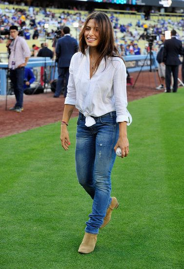 Improve Your Bleacher Style! See What Celebs Wear For Summer Sports: Actress Sarah Shahi picked an all-American ensemble to throw out the first pitch at Dodger Stadium, pairing classic blue jeans with Isabel Marant boots and a white button-up knotted at the waist.
