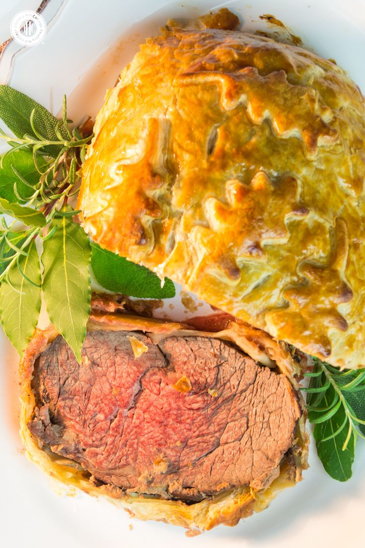 Beef Wellington is made with seared filet steak, layers of pâté and mushrooms, and baked in crispy puff pastry. This classic British dish is perfect for special occasions, and we love to serve it with Cumberland sauce. #recipe #steak #puffpastry | countryhillcottage.com