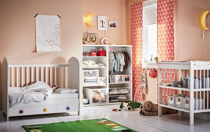 White and orange Toddler's room with crib in lower sleeping position with one side removed.