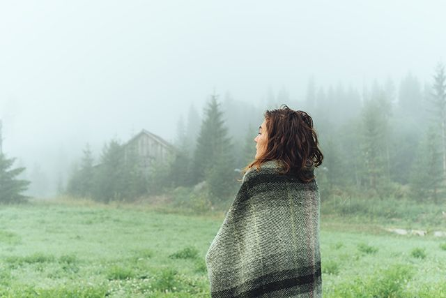 woman wrapped in a blanket on a misty field in the northern forest of Sweden © Rania Maria Photography