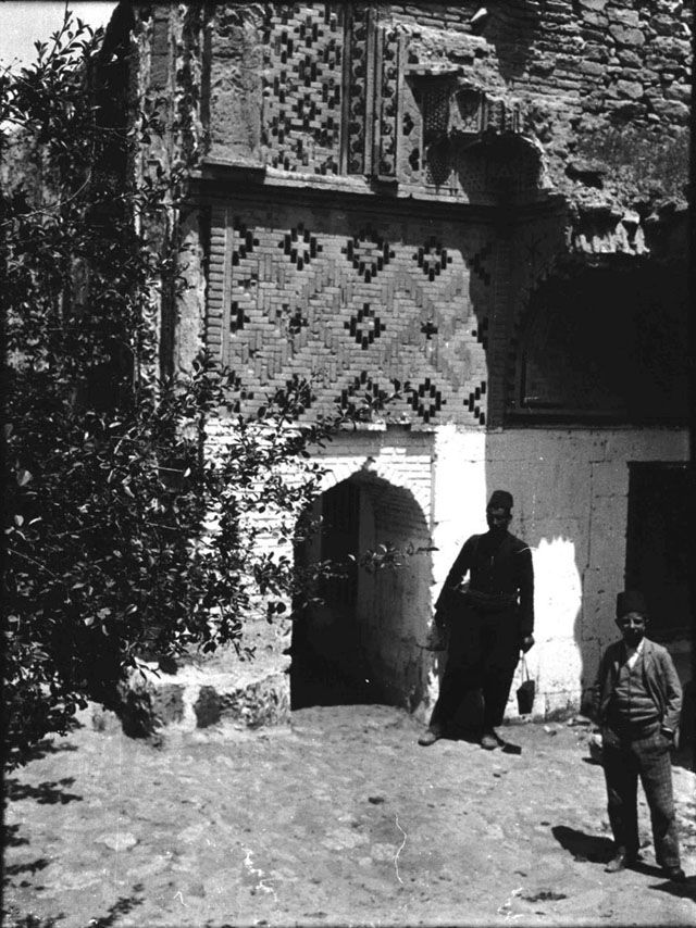 Konya Sırçalı Medrese built by Badr al-Din Muslih, tutor of Alâeddin Keykubad II. First large-scale structure in Anatolia to be decorated throughout with ceramic tiles. Chamber to right of Iwan with decorative tiles, Fattuh and boy in foreground. Date taken: May 1905	 Photographer: Gertrude Bell Location: Konya - Turkey. Subject date: 1243