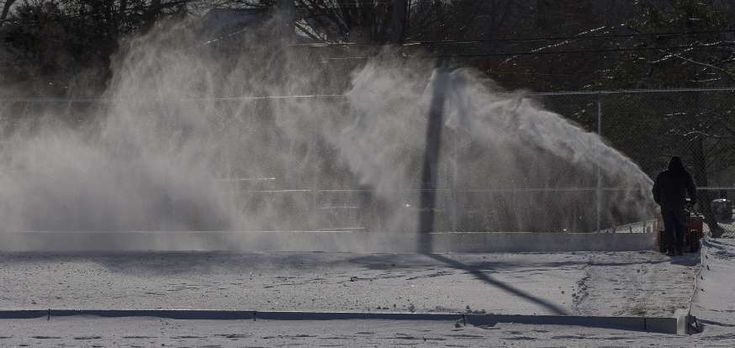 Winter Weather - BURLINGTON, MASSACHUSETTS -  A town recreational employee clears snow from an outdoor skating rink in Burlington, Massachusetts on Jan. 2. The region is still under an extreme cold with temperatures ranging from 5F