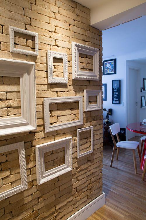 A entrada do seu apartamento não precisa ser uma parede sem graça. Essa parede trabalhamos com tijolo aparente e fizemos uma composição de molduras brancas.