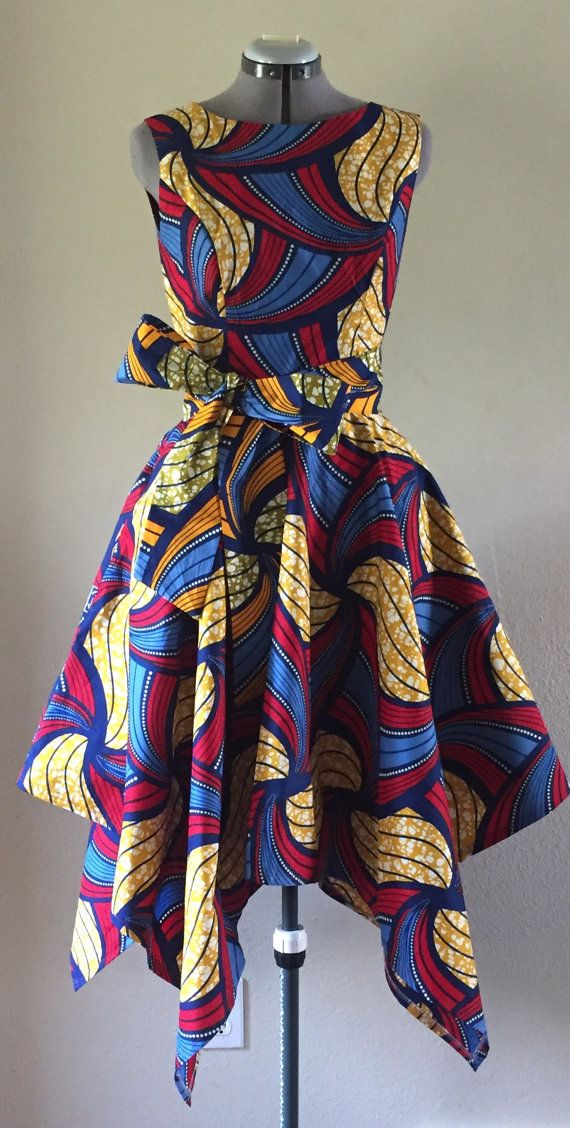 This cute little dress has a fitted bodice and a asymmetrical circle skirt that is fun and flirty. The dress bodice is fully lined. Vivid African Wax Print Dress With Asymmetric Cut Skirt and Optional Tie Belt Orange Red Blue Navy 100% Cotton (affiliate)