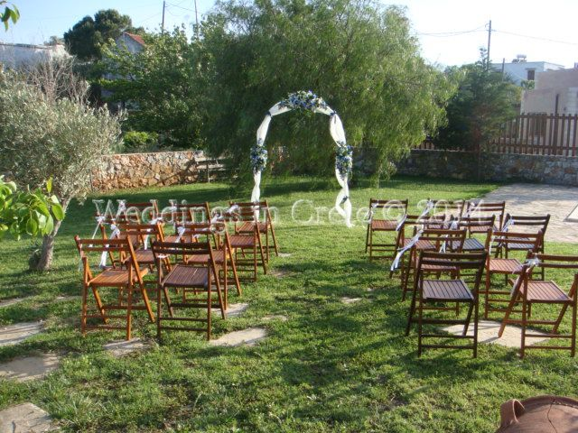Weddings in Crete - Wedding Arch and Brown Wooden Chairs with White Ribbon Bows.  Villa Chania area