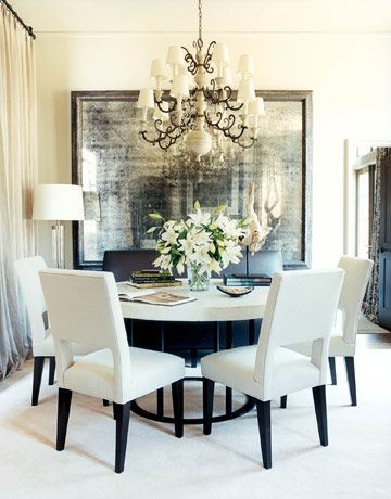 A seven-foot-wide foxed-glass mirror was made for the dining area to open up the space. Its dramatic scale is in perfect proportion with the Flemish wood and iron chandelier from Beckett Antiques, the table—a bone concrete top on an iron base by Bradley Hughes—and the Craig dining chairs by Hamilton. The sculpture is mounted driftwood.   - HouseBeautiful.com