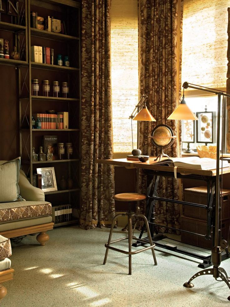 The dark-hued library was conceived as a more masculine workspace outfitted with a nineteenth century drafting table and a metal shelving unit. Tropical curtains and Batik-inspired sofa cushions lend a tropical vibe.