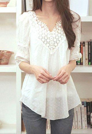 Blusa blanca larga con aplique puntilla en el escote.