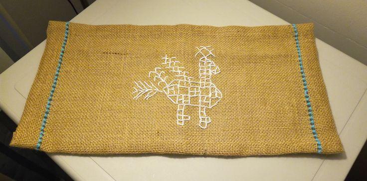 Säkkikankaasta reikä- ja  koristeompelein tehty liina.