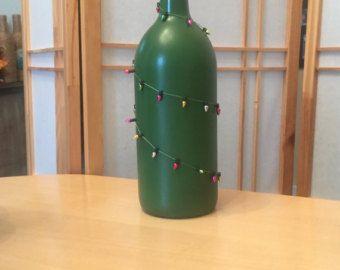 Botella de vino 1,5 L. Rociado en una pintura en aerosol verde. Adornado con un filamento de grano rojo con luces de colores.  ¡Ideal cumpleaños, Navidad, vacaciones, estreno de una casa, despedida de soltera o regalo de boda! Se trata de un gran equipamiento de hogar / decoración para tu estante, mostrador o de la chimenea.  No recogen gastos de envío para el local.