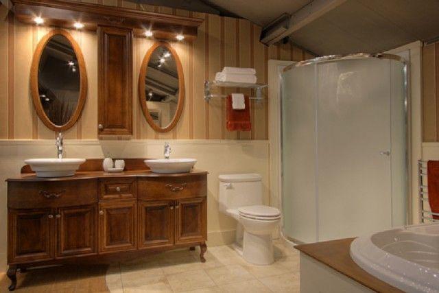 Salle de bain avec 2 lavabos et armoires en bois.