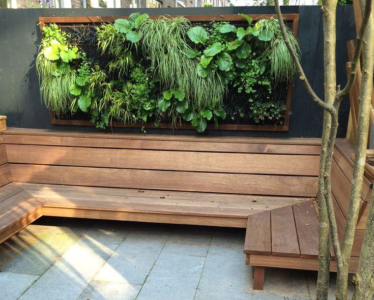 Groen schilderij met planten aan de wand in een kleine stadstuin en Amsterdam. Zithoek met houten loungebank op maat. Bestrating van stroken natuursteen. Ontwerp: Boekel Tuinen.