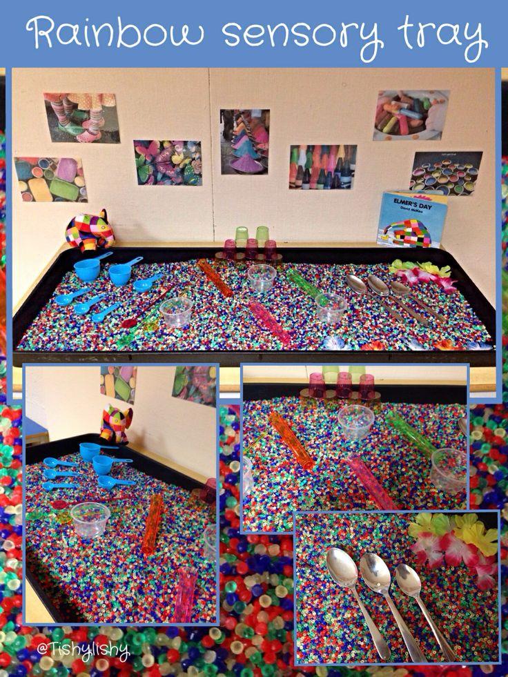 Begeleide of zelfstandige activiteit - Rainbow sensory tray. Added shot glasses, stirrers, measuring spoons, test tubes, silk flowers and Elmer!