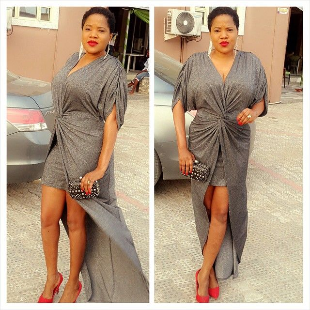 Nollywood actress, Toyin Aimakhu looks delectable in a sparkling grey twist wrap dress. The actress put her best foot forward in the stunning flowing dress and looks pretty delightful as she put on a pair of red court shoes, red lippy and red nails to brighten up the outfit.