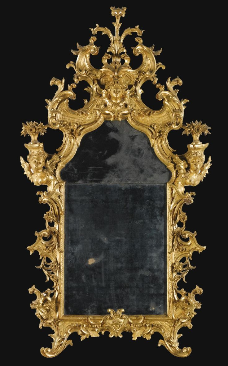 An Italian carved giltwood mirror, Tuscan, mid 18th century with a shaped divided plate within a frame carved with scrolls, flowers and foliage on a trelliswork ground, the scrolled cresting with a winged female mask, each corner with a winged female bust supporting a vase of flowers, the apron with an unidentifiable coat of arms
