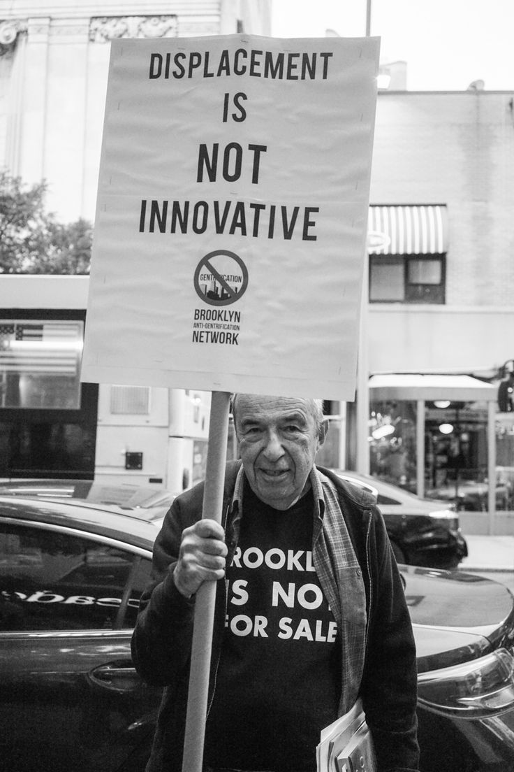 """""""Displacement is not innovative (Brooklyn Anti-Gentrification Network)""""  This anti-gentrification protester stands in downtown Brooklyn. Brooklyn has undergone radical changes and many People of Color, immigrants, poor and working class people can no longer afford to live in their homes. Their homes have been replaced by luxury buildings and venues, September 2016.  Photo credit: Cindy Trinh (http://activistnyc.tumblr.com/)"""