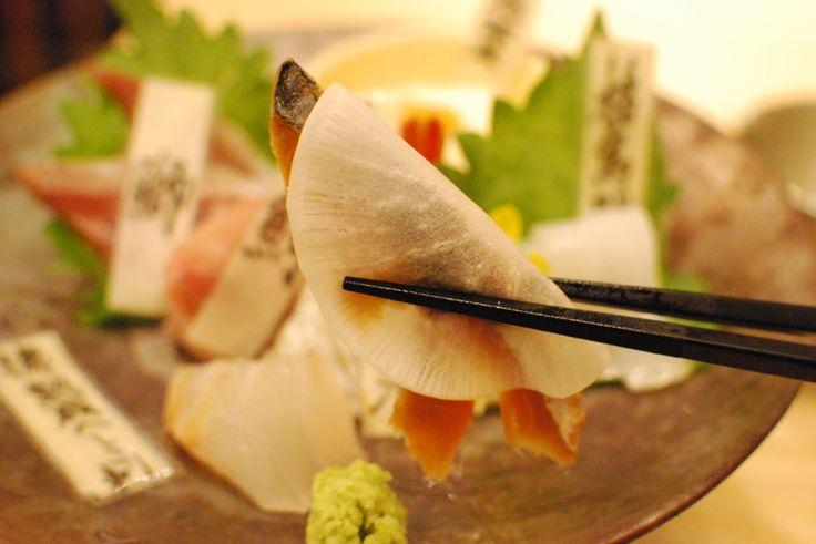 熟成魚の盛り合わせは、ブリ・マグロ・イカ・ウニのせ湯葉の他に、甘エビの昆布〆や小鯛の笹漬けなどもあり、鮮度の良い魚や漬けた刺身なども楽しめます。そして気になる熟成魚は、7日間熟成させたサゴシ・スズキ、そして大根にサンドされているのが美浜名物の「へしこ」です。  漁師さんたちの間では「鮪、鰤、白身魚は寝かせてから食べろ!」と言うのが常識なんだとか。寝かせることでタンパク質がアミノ酸へ分解され、旨みを極限まで高めることができるんだそう。  サゴシとは、サワラに成長する前の魚のことをいい、サワラ自体生で食べるということが少ないと思うのでこれは珍しい。熟成されたサゴシはトロッとしたした舌触りと独特の旨味があり、スズキはねっとりとした食感と甘みが不思議と増していてお酒が進みます。  美浜町名物「へしこ」は薄切りにスライスされた大根でサンドして食べます。糠漬け特有の香りとしょっぱさが、痺れるくらい美味しい。これはお酒をお代わりせざる負えません!!