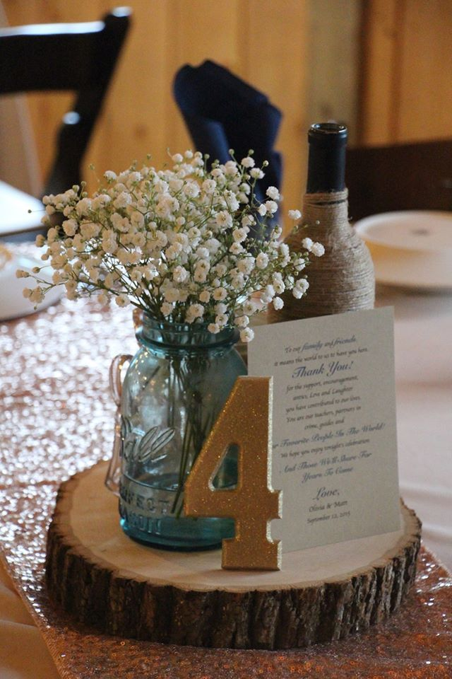 Weatherington Woods, Zanesville, Ohio. Rustic venue. Rustic center piece on a wood slab, mason jar, babies breath, twine wrapped wine bottle, gold sparkle table number, thank you note from bride and groom.