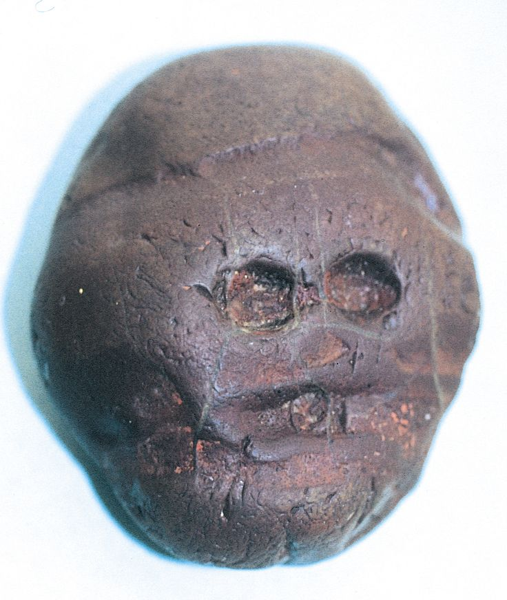 """First known """"art"""" object: Waterworn pebble resembling a human face, from Makapansgat, South Africa, ca. 3,000,000 BCE. Reddish brown jasperite, approx. 2 3/8"""" wide."""