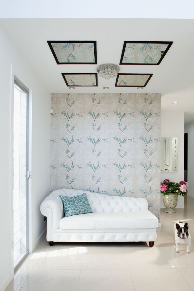 A cozy hallway corner with a white chaise lounge in a white modern home.