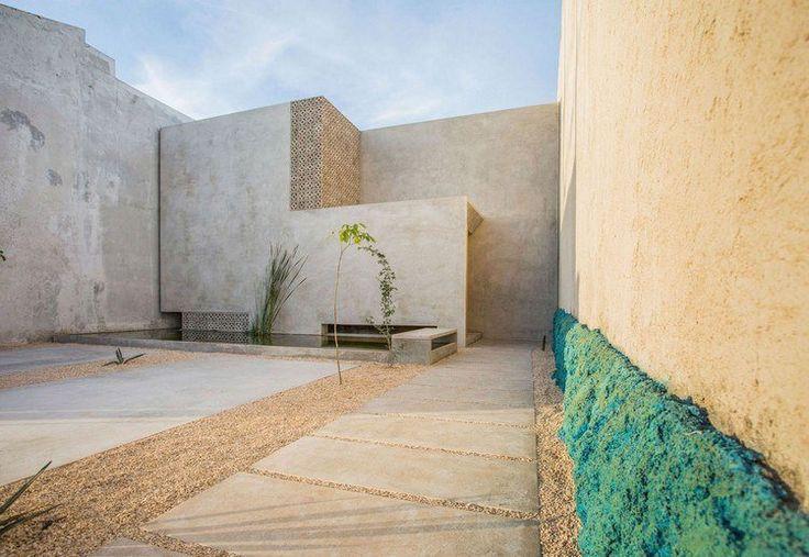 petit jardin avec une allée en dalles de béton et gravier décoratif entouré de murs habillés d'enduit extérieur en ciment