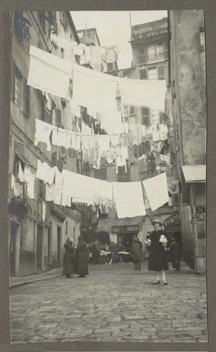 Anonymous   Vrouw poserend in een straat met drogend wasgoed, Anonymous, 1920 - 1930   Een vrouw poseert onder wasgoed dat tussen huizen hangt. Op de achtergrond een winkel met opschrift 'Sale e tabacchi' (zout en tabak), daarom een Italiaanse stad, mogelijk Genua. Onderdeel van Familiealbum Nederlands-Indië.