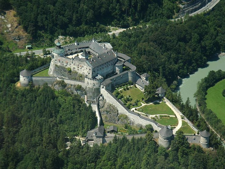 """Aerial shot of the Castle Hohenwerfen. Hohenwerfen Castle (German: Burg Hohenwerfen) stands high above the Austrian town of Werfen in the Salzach valley, approximately 40 km (25 mi) south of Salzburg. The castle is surrounded by the Berchtesgaden Alps and the adjacent Tennengebirge mountain range. The fortification is a """"sister"""" of Hohensalzburg Castle both dated from the 11th century."""