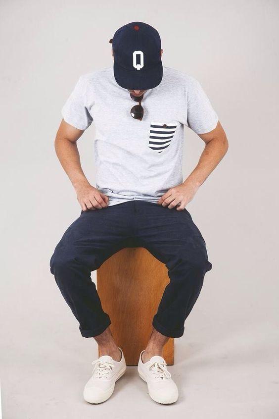 Comprar ropa de este look: https://lookastic.es/moda-hombre/looks/camiseta-con-cuello-barco-pantalon-chino-zapatillas-bajas-gorra-de-beisbol-gafas-de-sol/11010 — Gorra de Béisbol Estampada Azul Marino y Blanca — Gafas de Sol Marrón Oscuro — Camiseta con Cuello Barco Gris — Pantalón Chino Azul Marino — Zapatillas Bajas Blancas