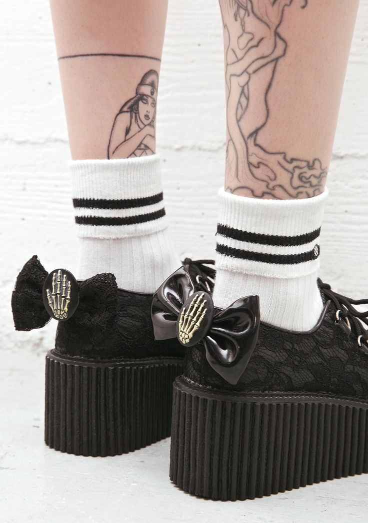 """Demonia Elvira's Bow Lace Ceepers cuz evil walks with yew. Tread sinfully with these badazz creepers featuring a beautiful lace overlay, detachable lace bow with a skeleton hand cameo, and 3"""" creeper platform. With a D-ring lace up and piping detail, these shoes will have yer each step have an edge."""