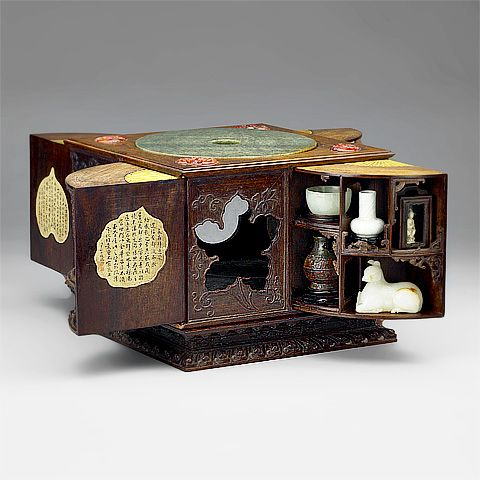 """Square Sandalwood Curio Box (with 30 curios inside)  Ch'ien-lung Reign (1736-1795), Ch'ing Dynasty (1644-1911) Length: 25 cm, width: 25 cm, height: 21 cm        When closed, this curio box looks like a plain container. The advantage to this type is that it does not take up much space in storage. Although the outside appears quite simple, it is by no means monotonous. The reason lies in the decorative method of using """"panels"""" by the artisans who made it. On the one hand, they allow the…"""