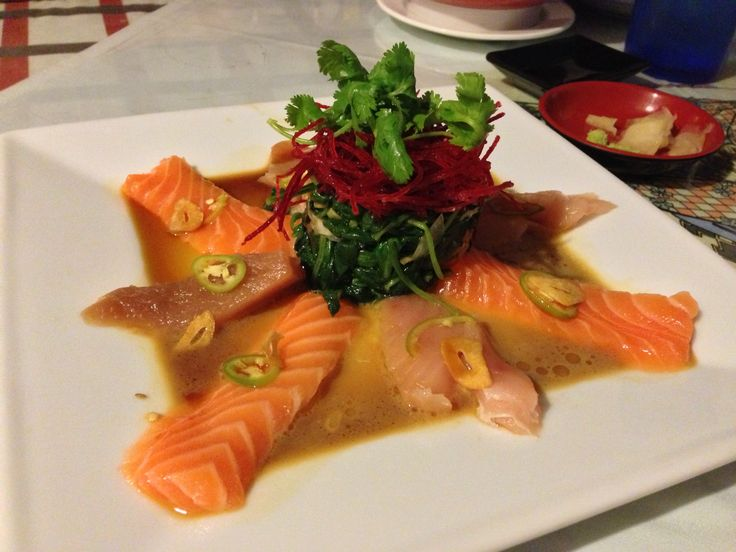 Salmon and Tuna sashimi appetizer, with fried garlic, sautéed spinach with garlic and avocado