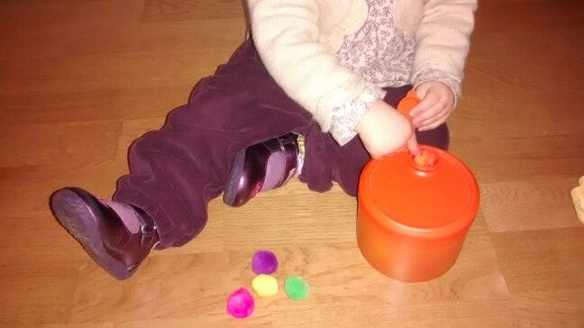 Tupper y pompones: se introducen los pompones por la abertura redonda de la tapa de un tupper.
