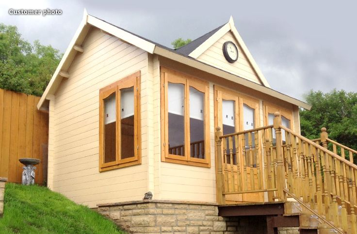 A customer photo showing how they have sited the Wye clockhouse style summer house on a raised platform on a hill, with steps leading to the doors - http://www.gardenlifelogcabins.co.uk/products/chloe-wye/product-details.php