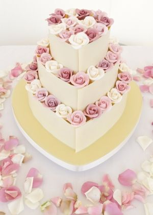 Three tier heart shaped cake coated in pure white couverture chocolate. Decorated with hand-made sugar pink Coolwater roses and ivory roses. -beautiful-