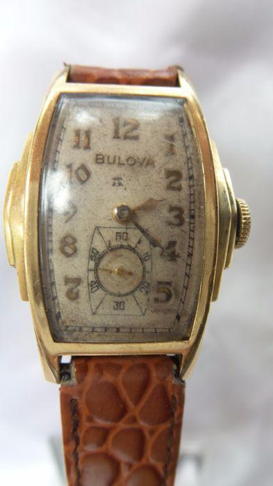 """Bulova Fifth AveTank Watch 1939(10AE).  Heel bijzondere langwerpige polshorloge van Bulova gemerkt met Bulova Fifth Ave New York uit 1939(volgens gemerkt 10AE op uurwerk)Dit horloge heeft een beige wijzerplaat met mooie """"gouden""""Arabische cijfers en """"gouden""""wijzers(3) en """"gouden""""Bulova merk.De zijkanten lopen mooi trapsgewijs naar """"onder"""".De achterkant(de deksel)is eveneens verguld en gaaf.Aan de bovenkant staat gegraveerd B-10K Gold Filled en aan de onderkant 024755Op het uurwerk staat…"""
