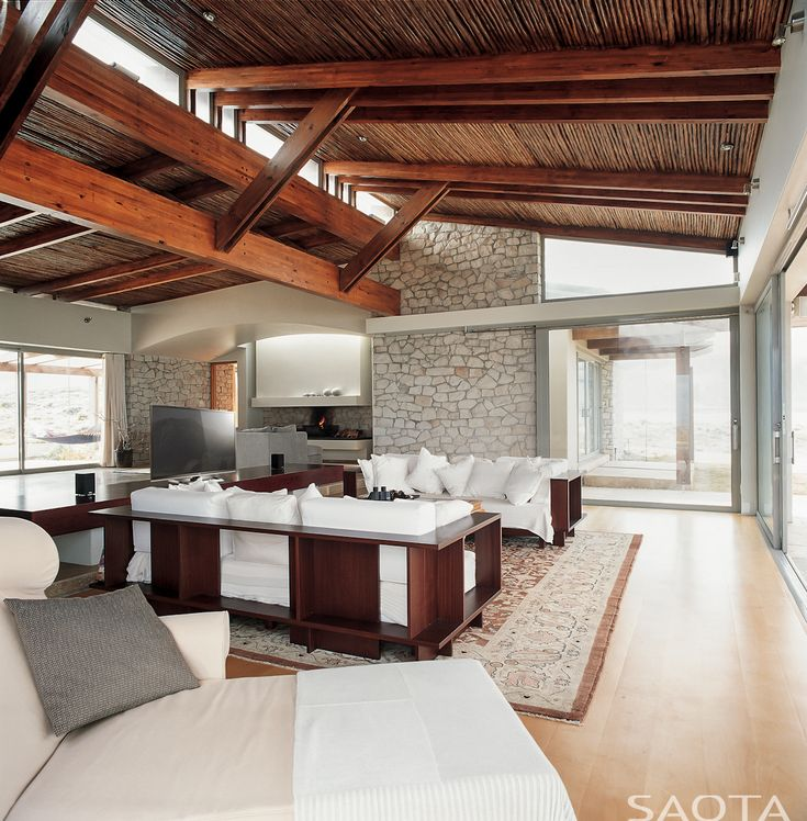 A beautiful living room with shelving around the outside of the sofas.  What do you think of the wooden ceiling? Designed by http://www.saota.com/