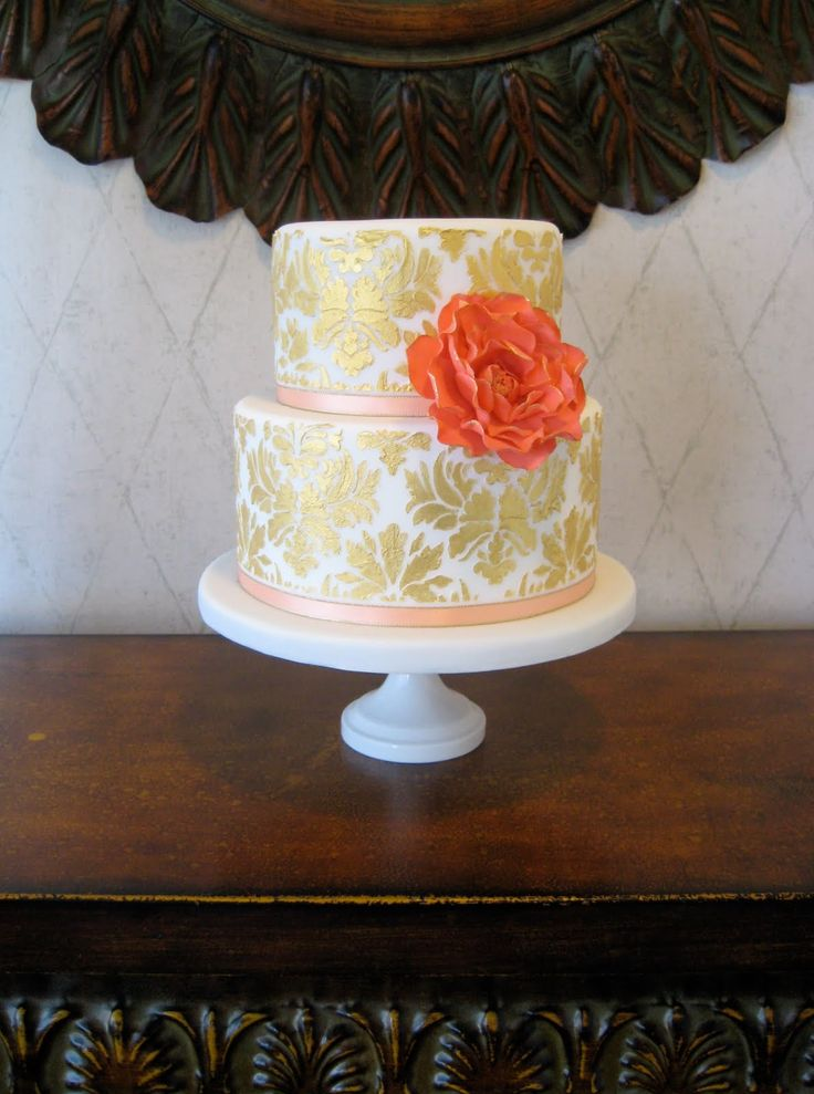 White and gold damask wedding cake with coral rose.
