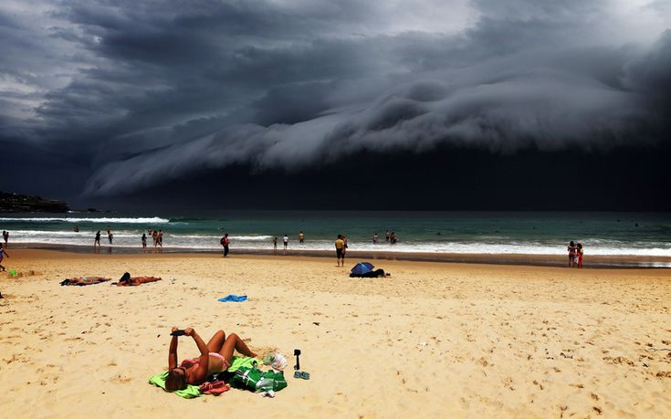 Sunbathers soak up the last few rays of sunshine on Bondi Beach before storm clouds move in over Sydney, New South Wales Picture: Rohan Kelly/Newspix/REX Shutterstock