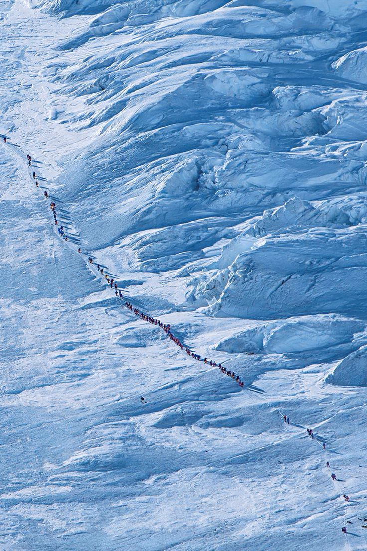 A crowd of climbers slog up the Lhotse Face, heading toward Camp IV on the Mount Everest.      Photo by Andy Bardon. (via nationalgeographic)