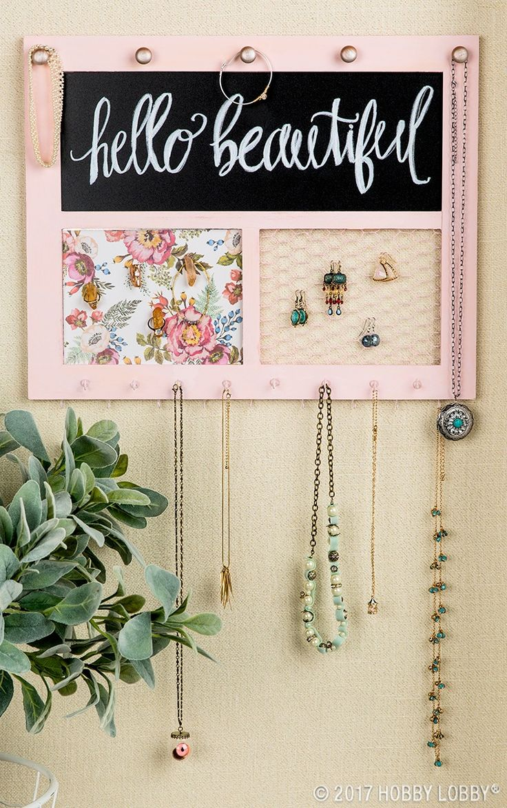 Create the perfect organization space for your jewelry and put your collection on display with this customizable frame!  To DIY: 1. Paint wood frame. 2. Add colorful scrapbook paper to cover metal. 3. Glue knobs to top. 4. Paint and attach screw hooks. 5. Embellish magnets as desired (we used quartz!)