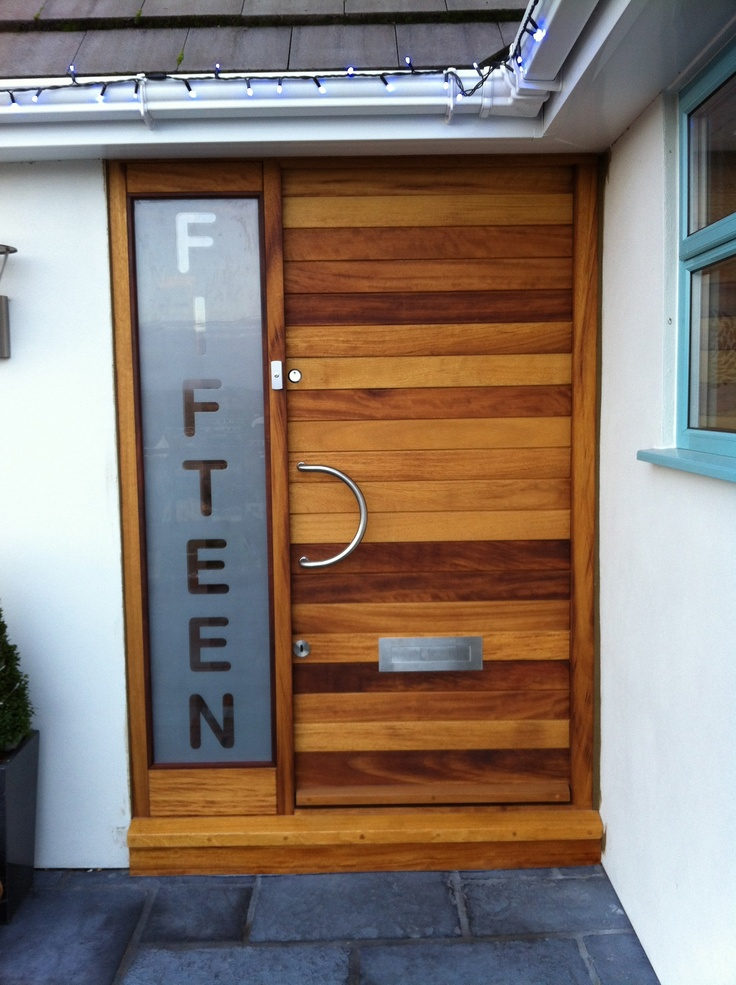 Iroko hardwood front door assembly with glazed panel incorporating house number. Manufactured by Devon Custom Joinery