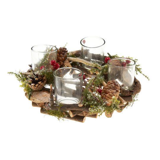 Candeliere a corona con quattro bicchieri in vetro porta candele votive. Corona composta da pigne, legnetti, rametti di pino e bacche. Lieve effetto innevato. Diametro: 23cm.