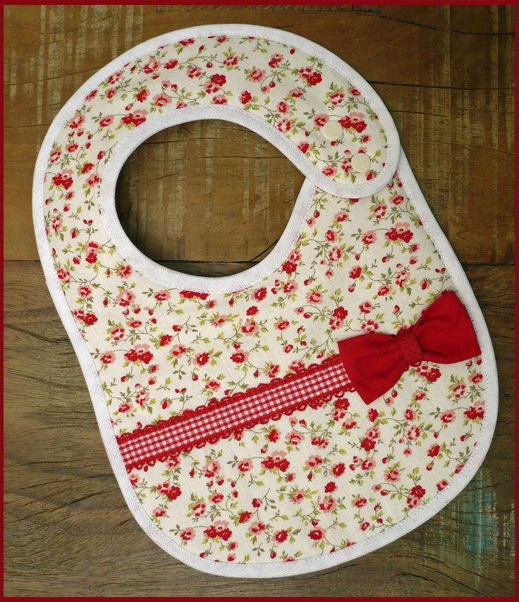 Babador vermelho em Patchwork com fitinha decorativa e laço. Tecidos 100% algodão, forrado com manta acrílica. Fechamento com botões de pressão, duas regulagens.