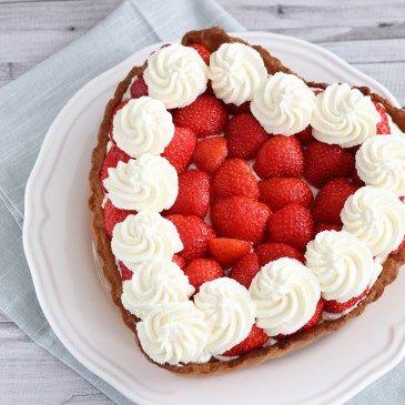 Een heerlijke taart in hartvorm, leuk voor Valentijnsdag of Moederdag.     Print recept Harttaart met aardbeien Ingrediënten 1 ei 3 eidooiers 500 gr aardbeien 250 gr bloem 200 gr suiker 150 gr zachte boter snufje zout 1 tl vanille extract 2 gr bakpoeder 500 ml volle melk 1 vanillestokje 40 gr maizena …
