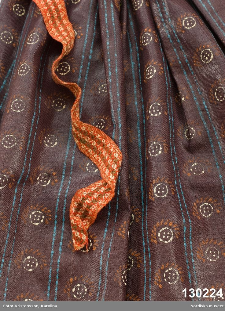 """Förkläde av mörklila tunn yllekypert av kamgarn med starkt glättad yta, s.k. rask eller chalon. har fått ett sekundärt stämpeltryckt mönster med oljefärg, smala dubbla  ränder  i klarblått och mellan ränderna rader av  """"rosor"""" dvs. mönsterfigurer i vitt och rött. Rynkat i midjan med ett påsytt  3 cm brett midjeband i ylle smårutigt  i rött, grönt och vitt av den sort som kallas Malsband dvs. Malungsband. Nederkanten inskodd med  smalrandigt halvylletyg i grått och grönt/ljusgult. Handsömnad…"""