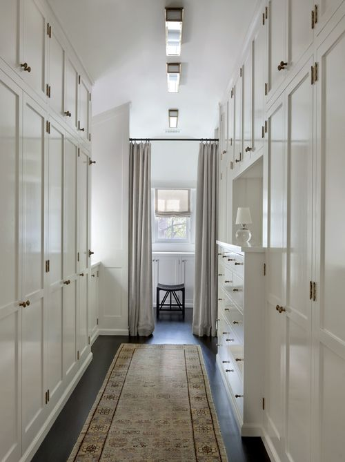 Long And Narrow Walk In Closet Boasts Floor To Ceiling Wardrobe Cabinets  Adorned With Brass Hardware Facing A Built In Dresser Illuminated By A Row  Of Long ...