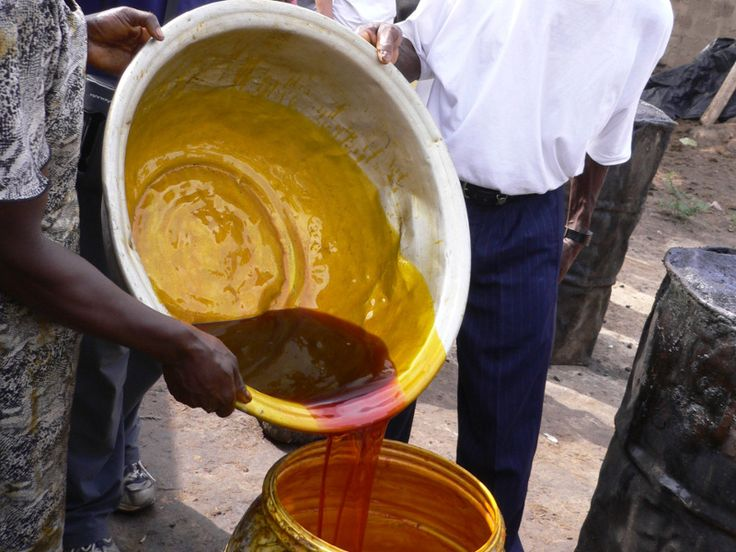 Pouring red palm oil into a storage vessel
